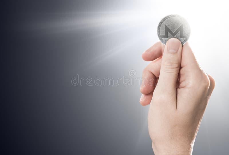Вручите держать монетку Monero на нежно освещенной предпосылке с космосом экземпляра иллюстрация вектора