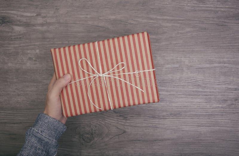Вручите держать подарочную коробку на деревянном на рождество и счастливый Новый Год стоковые фото