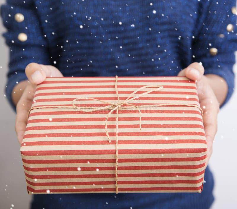 Вручите держать присутствующий подарок красный год сбора винограда и украшенное рождество стоковое изображение