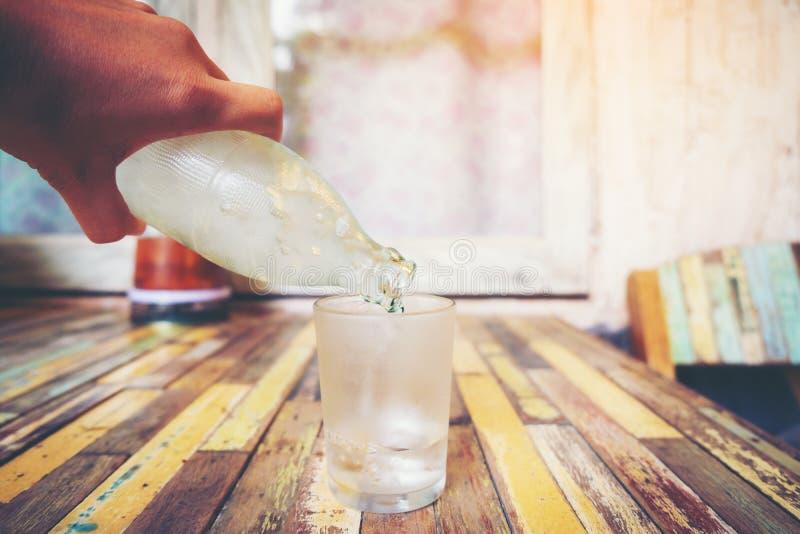 Вручите держать стеклянную бутылку воды холодная и лить вода внутри стоковая фотография rf