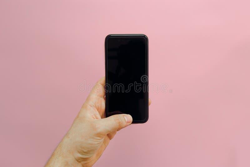 Вручите держать стильный черный телефон с пустым экраном на розовом backg стоковые изображения rf