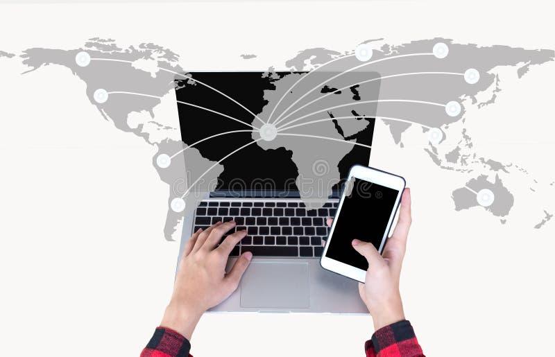Вручите держать умный телефон и используйте портативный компьютер на сети карты мира для сообщения, стоковое изображение rf