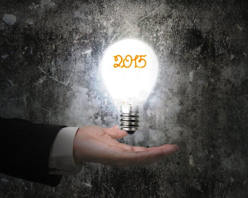 Вручите держать бетонную стену загоренную электрической лампочкой 2015 темную старую стоковая фотография