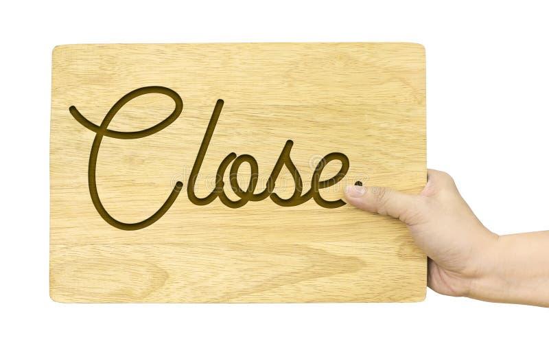 Вручите держать деревянную плиту с близким словом изолированный на белом backgr стоковое изображение