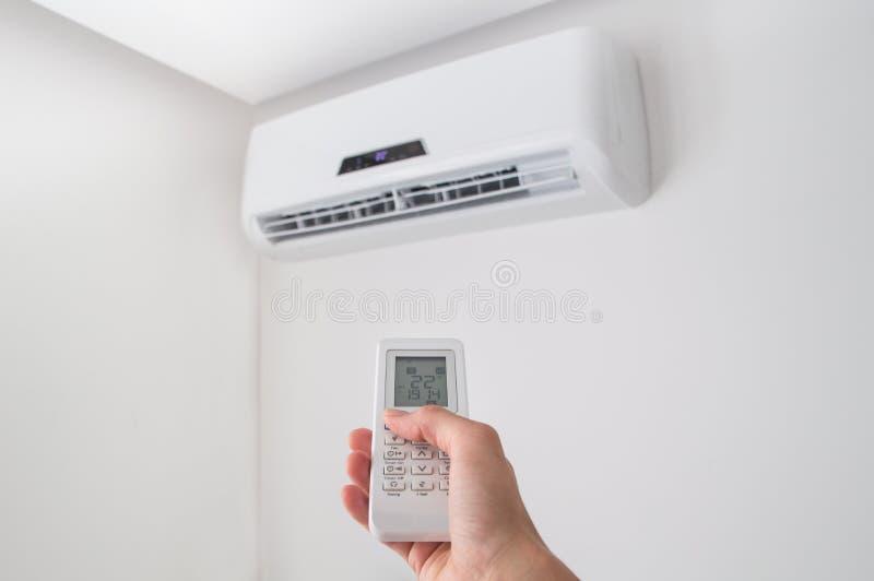 Вручите держать дистанционное управление для кондиционера воздуха на белой стене стоковые фото