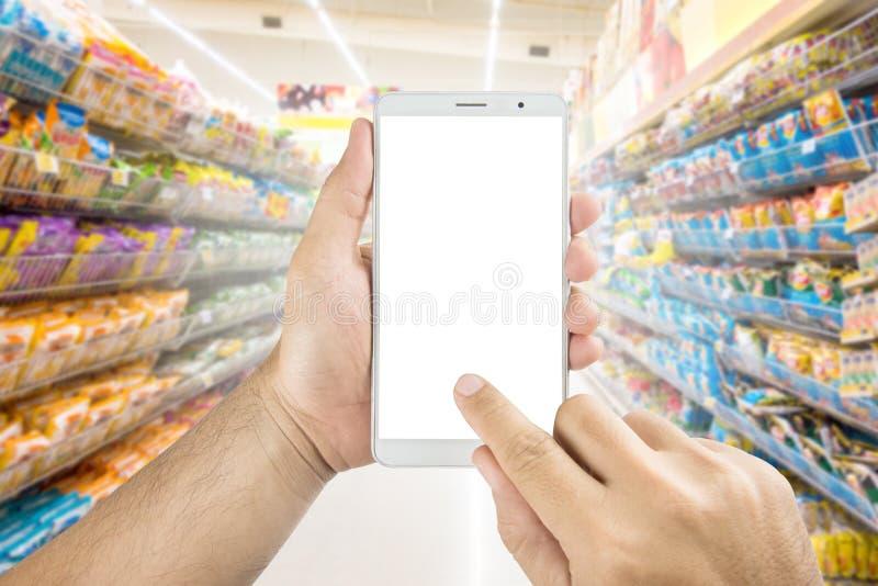 Вручите держать и использование умный телефон с изолированным экраном с покупками неясного изображения в супермаркете стоковое фото