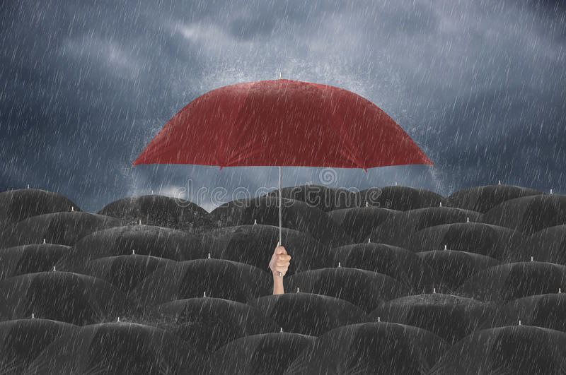 Вручите держать красный зонтик различный среди черного зонтика стоковая фотография rf