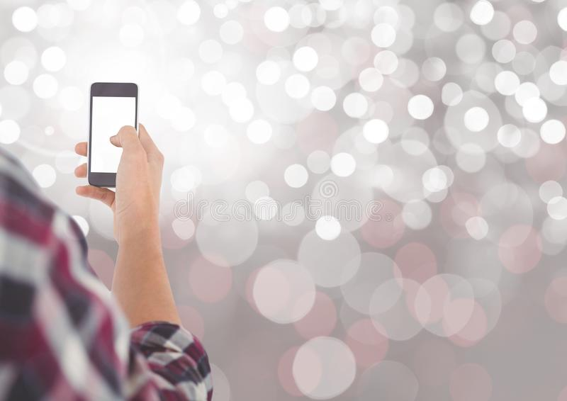 Вручите держать мобильный телефон с сверкная светлой предпосылкой bokeh стоковые фотографии rf