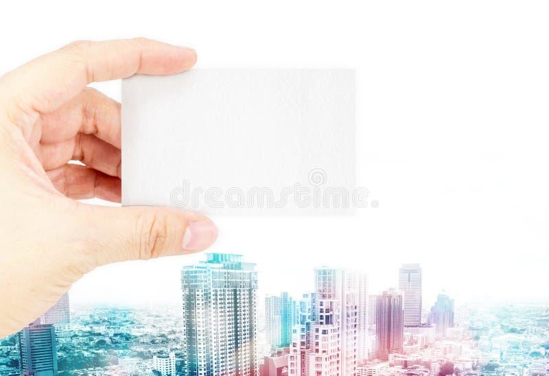 Вручите держать пустую визитную карточку с слишком покрасьте с cityscap стоковое фото