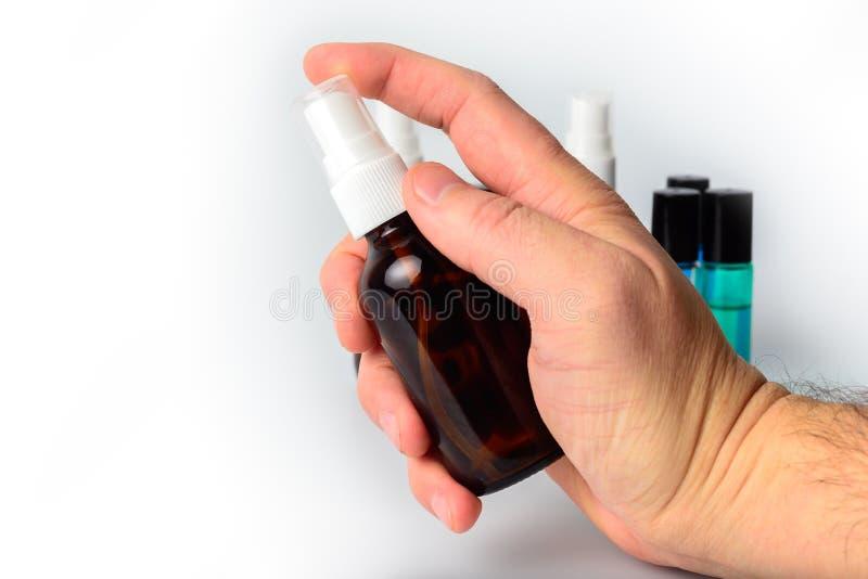 Вручите держать стеклянную бутылку брызга с бутылками в предпосылке стоковое фото rf