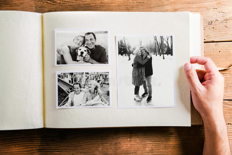 Вручите держать фотоальбом с изображениями старших пар студия стоковые фото