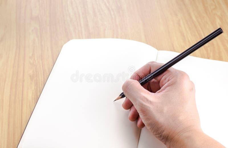 Вручите держать черное сочинительство карандаша на пробеле открытая тетрадь дальше сватает стоковое изображение rf