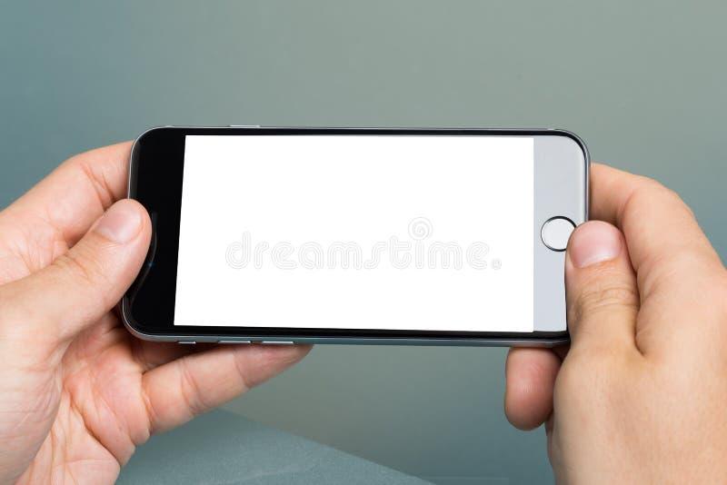 Вручите держать iPhone 6 Яблока с пустым экраном стоковое изображение rf