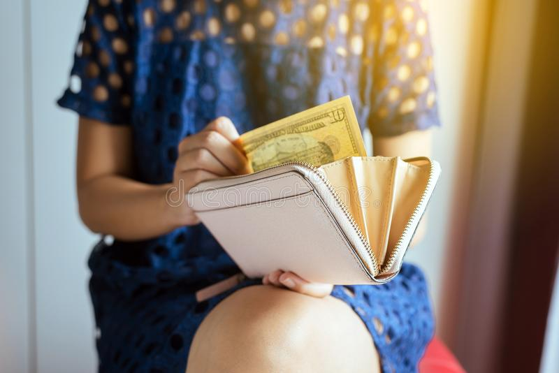 Вручите женщину подсчитывая счеты доллара США в бумажник стоковые фото