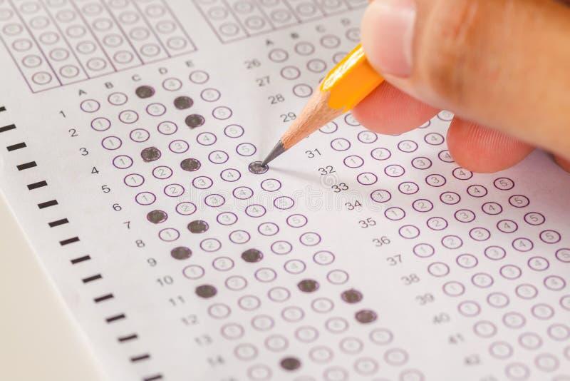 Вручите заполните внутри лист и карандаш компьютера копировальной карбоновой бумаги экзамена стоковые фото