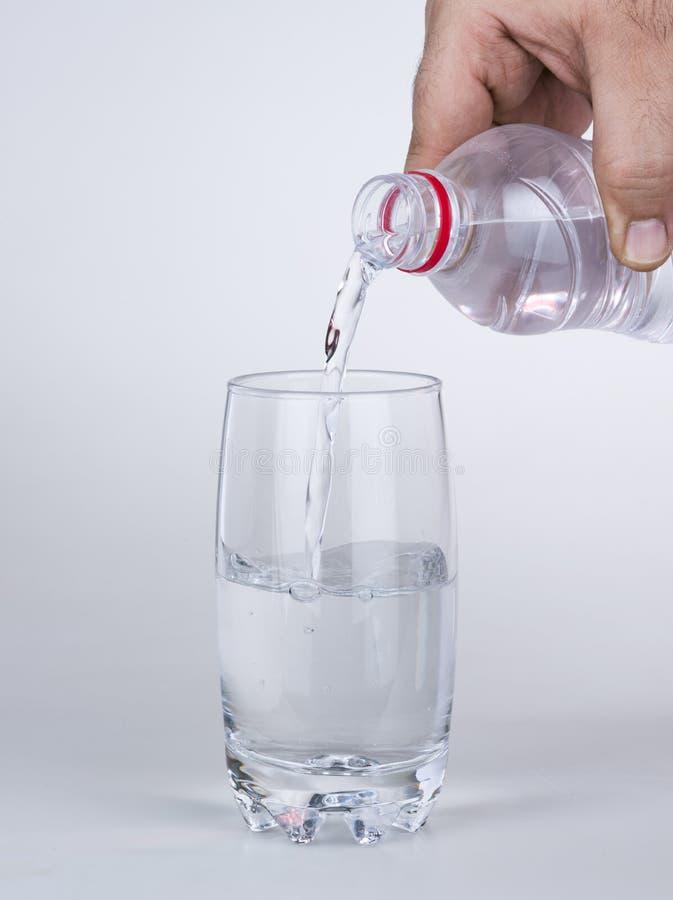 Вручите лить воду к стеклу от пластичной бутылки стоковые изображения