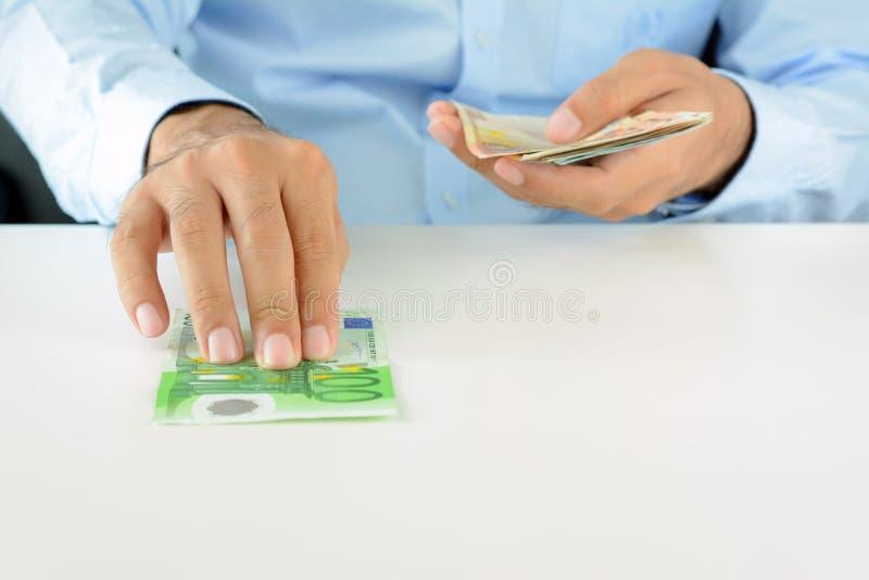 Вручите нажатие денег, валюты евро (EUR), на белом столе стоковая фотография