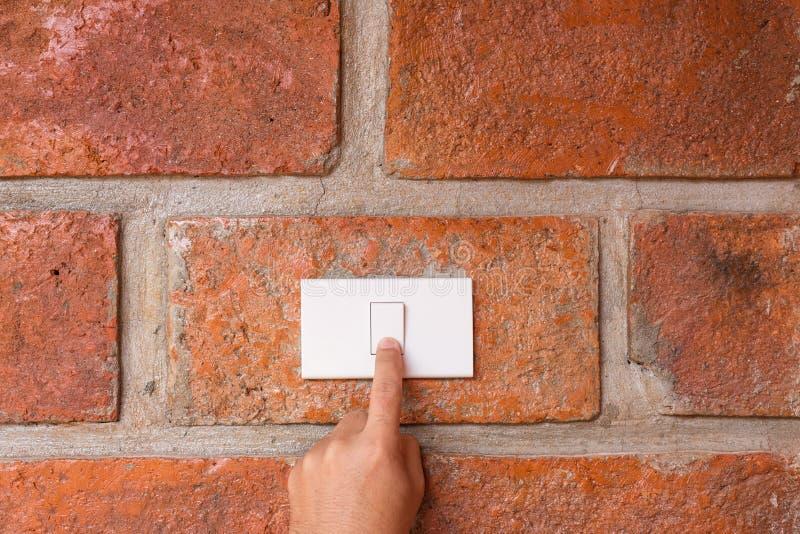 Вручите поверните выключатель на красной стене стоковое фото