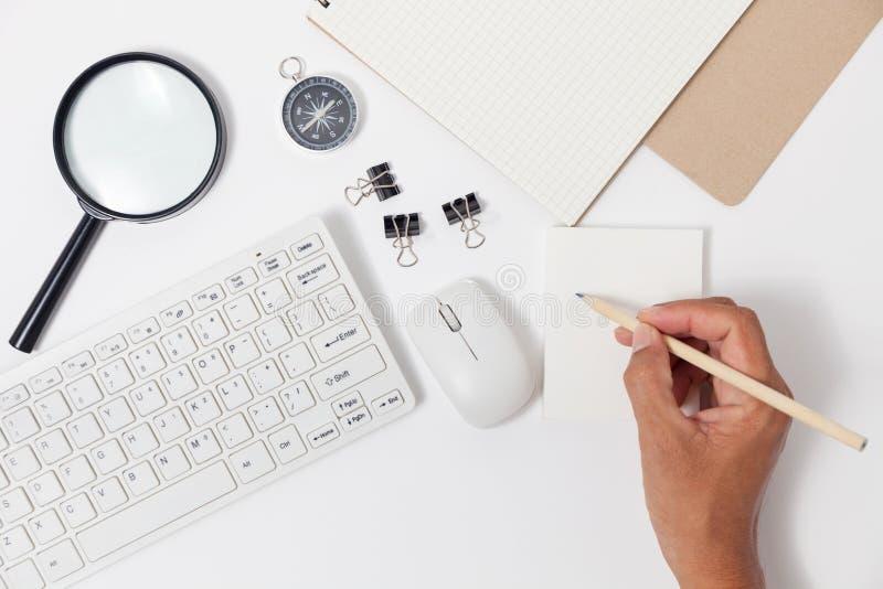Вручите сочинительство карандаша пользы на объектах примечания и дела белой бумаги стоковое изображение
