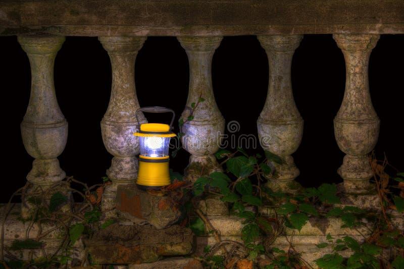 Вручите фонарик около балюстрады покинутого ресторана на держателе Ak стоковая фотография rf