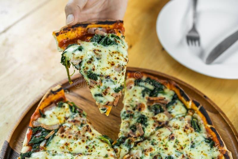 Вручите хватать часть пиццы шпината и козий сыра на деревянном столе стоковая фотография