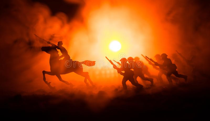 Всадник офицера мировой войны (или ратника) на лошади с шпагой готовой для боя и солдатами на темной туманной тонизированной пред стоковая фотография rf
