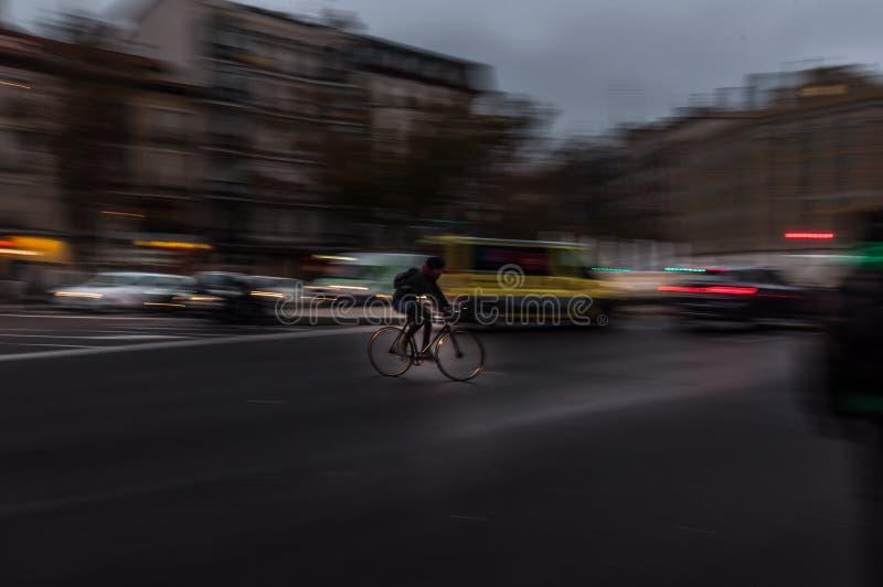 Всадник Bicicle ехать быстро в большом городе стоковая фотография