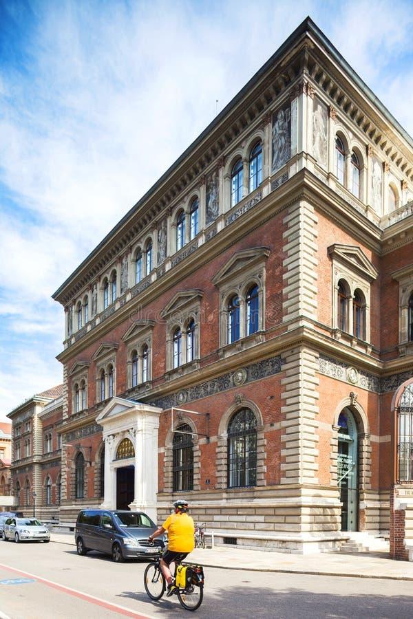 Всадник велосипеда едет рядом с музеем декоративноых-прикладн искусств, современным искусством MAK австрийским в вене. стоковые фотографии rf