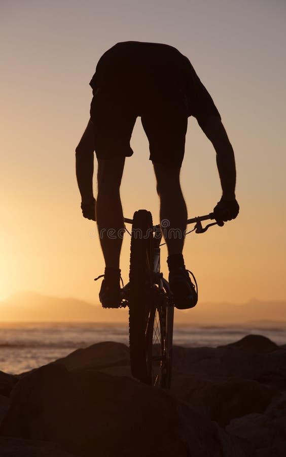 Всадник горного велосипеда и заход солнца Южная Африка стоковое фото