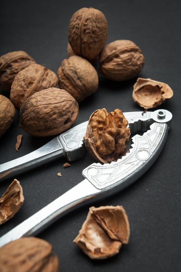 Все грецкие орехи и слезанный, Щелкунчик на черной предпосылке стоковое изображение rf