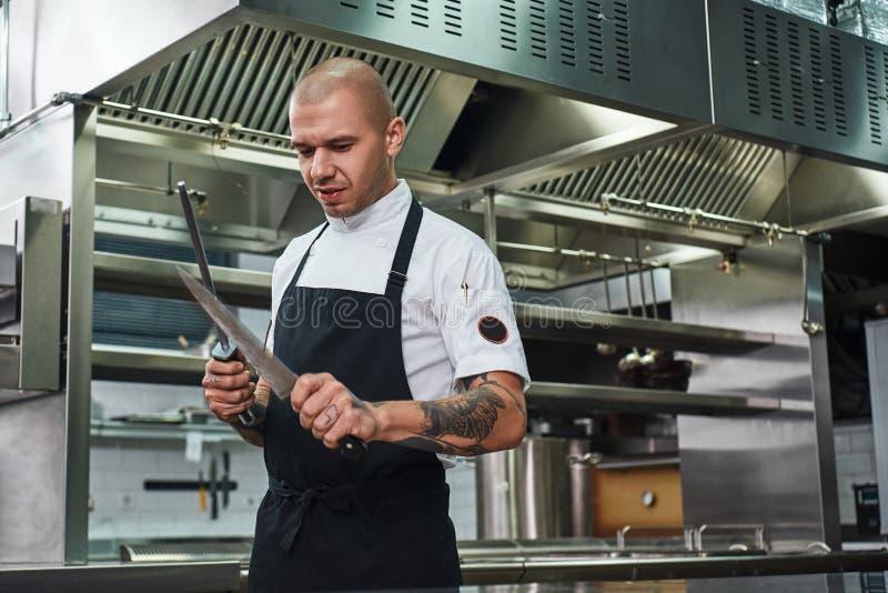 Все должно быть идеальным зверским шеф-поваром с несколькими татуировок на его оружиях точить нож пока стоящ в a стоковые фото