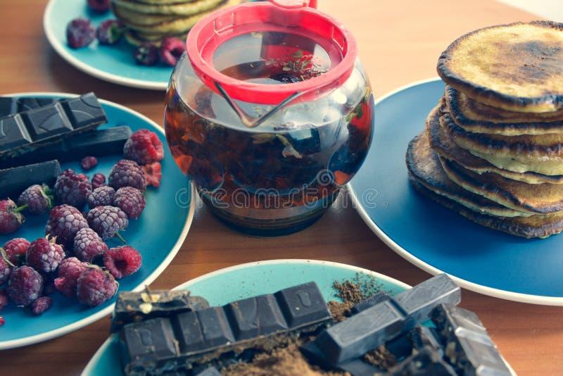 все еще жизнь на голубых тарелках блинчики с горохом, грелый шоколад, шоколадные батончики, вареный чай стоковое фото rf
