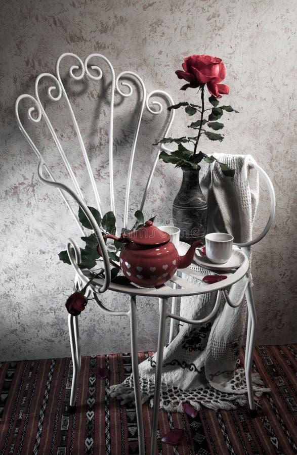 Все еще жизнь с античным стулом, розово и чаем стоковое фото