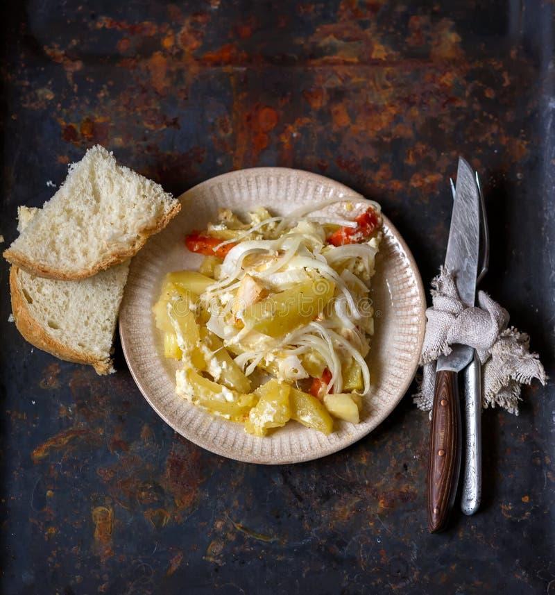 Картошки и лук испекли послужено с отрезанными хлебом, вилкой и knif стоковая фотография