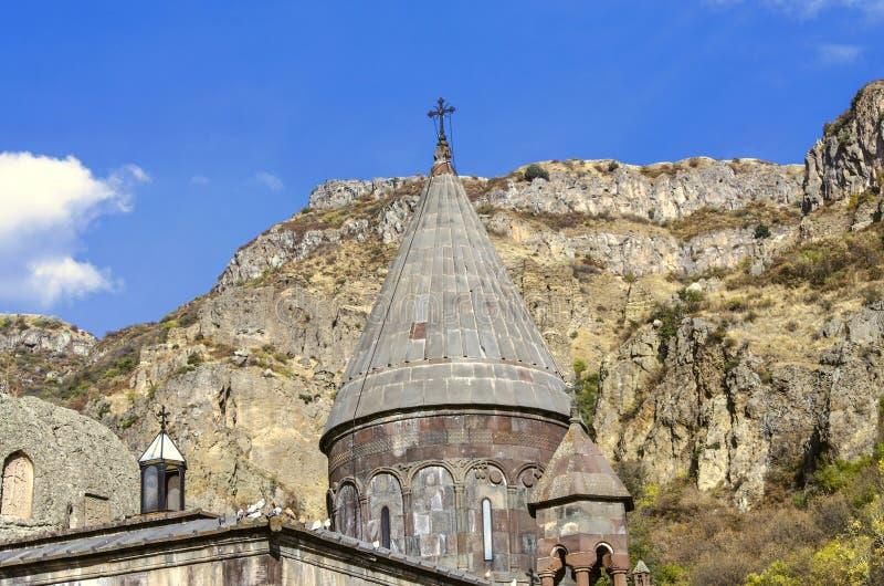 Все куполы с крестами и церковь пещеры с высекаенными khachkars на стенах, в монастыре Geghard в Армении стоковое изображение