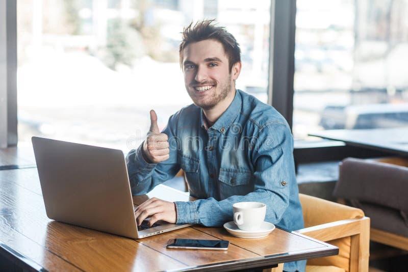 Все alright! Портрет красивого удовлетворенного бородатого молодого фрилансера в рубашке голубых джинсов сидит в кафе и работает  стоковые изображения