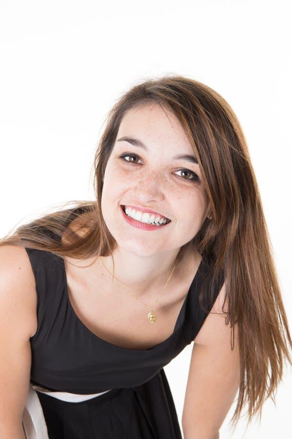 Вскользь девушка брюнет женщины смотря с улыбкой на белой предпосылке стоковое фото
