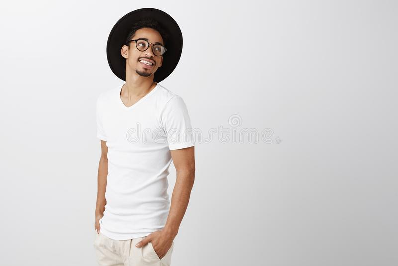 Вскользь рабочий день известной модели Портрет человека стильной пригонки темнокожего в ультрамодных стеклах и шляпе, смотря в ст стоковое фото rf