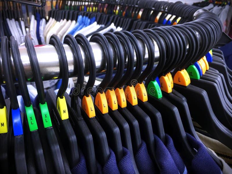 Вскользь рубашки на вешалках с ярлыками письма размера на изогнутом стальном шкафе стоковое изображение