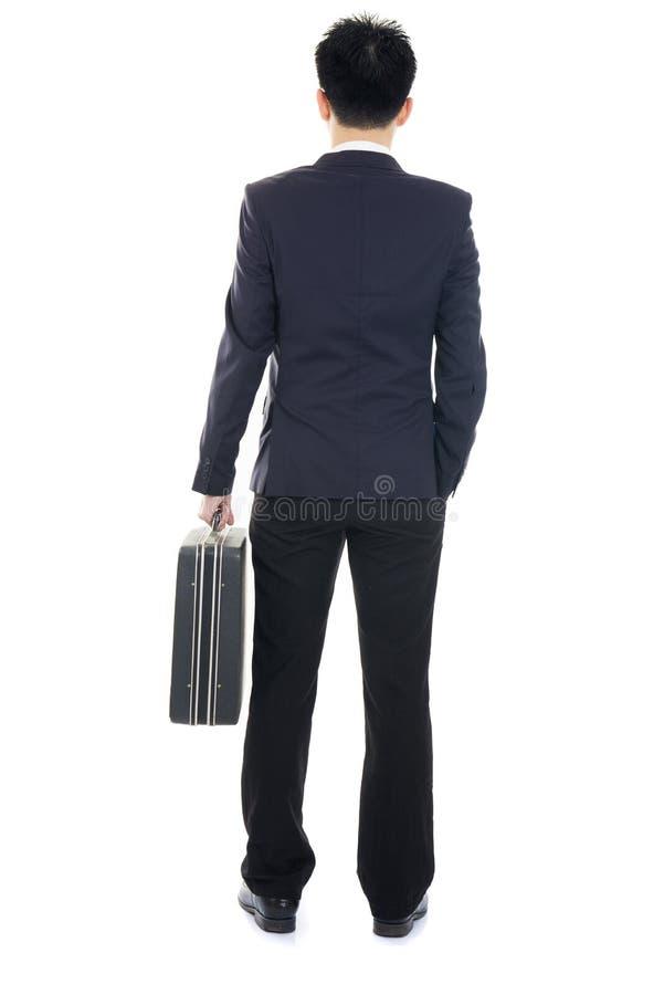 Вскользь азиатский взгляд задней части бизнесмена изолированный на белизне стоковое фото rf