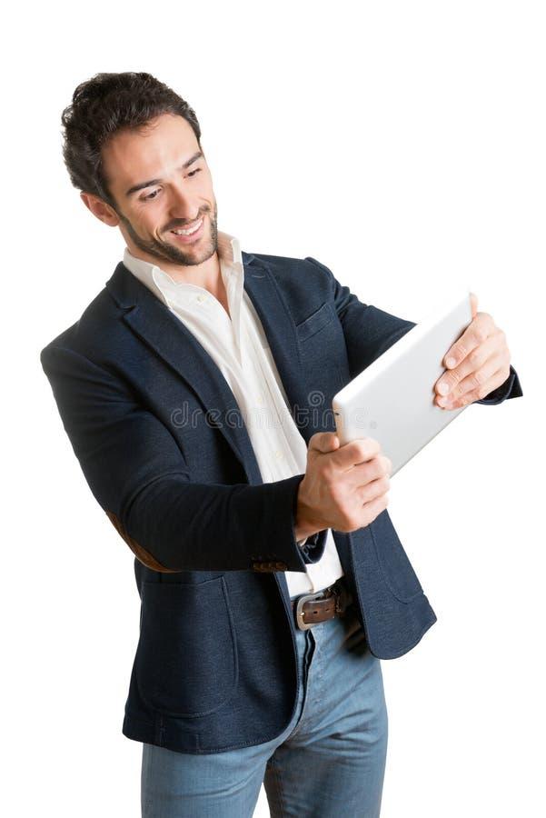 Вскользь бизнесмен смотря таблетку стоковое изображение