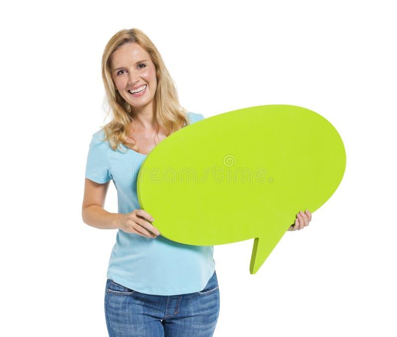 Вскользь женщина держа пузырь речи стоковое фото rf