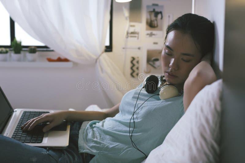 Вскользь молодая женщина спать на кровати пока использующ компьтер-книжку дома стоковая фотография