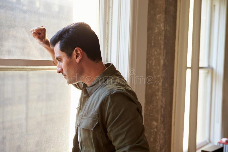 Вскользь одетый бизнесмен смотря из окна офиса стоковое изображение