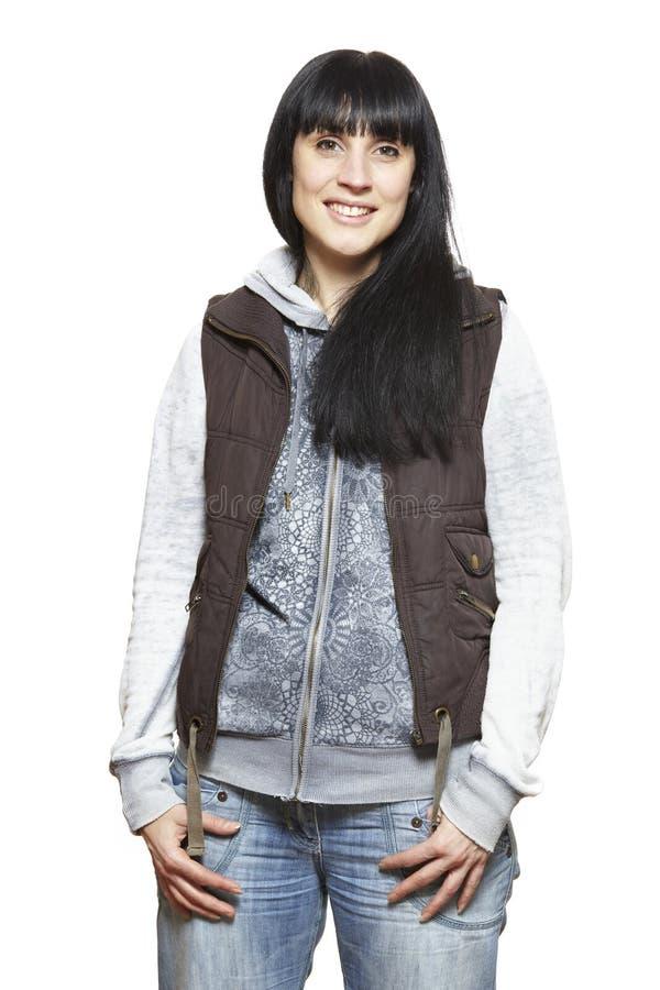 Вскользь одетый усмехаться молодой женщины стоковое изображение