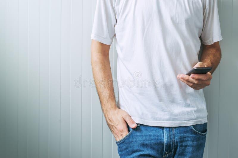 Вскользь человек в белой футболке используя мобильный телефон стоковое изображение