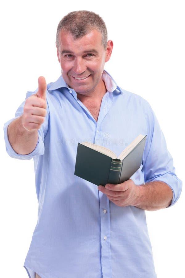 Вскользь человек постаретый серединой показывает о'кеы, с книгой стоковое изображение