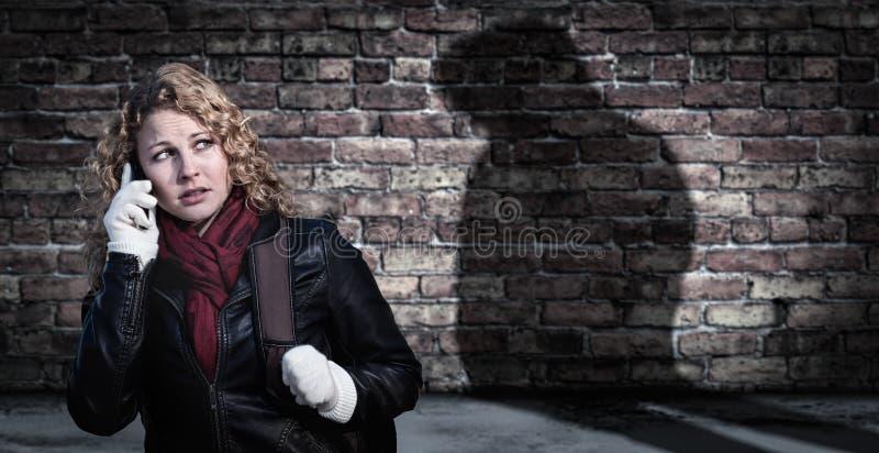 Вспугнутая молодая взрослая женщина использует сотовый телефон как загадочная мужская диаграмма тени скрывается рядом стоковая фотография
