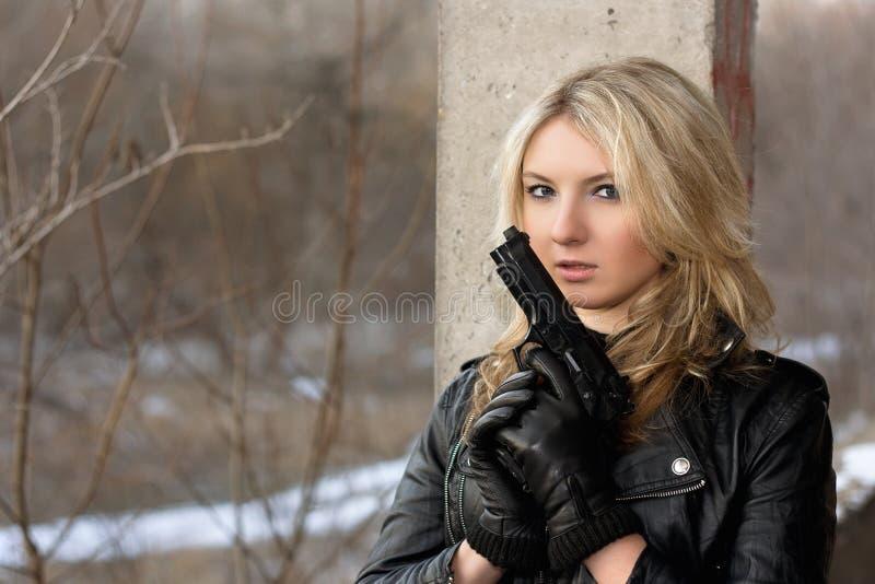Вспугнутая молодая женщина с оружием стоковое фото rf