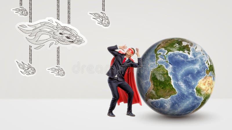 Вспугнутый бизнесмен в красной накидке сжимаясь под нападением бумажных комет с глобусом за им стоковые изображения